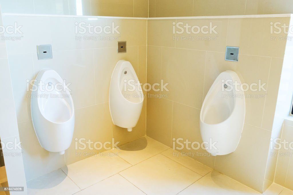 Urinals in public toilet in white stock photo