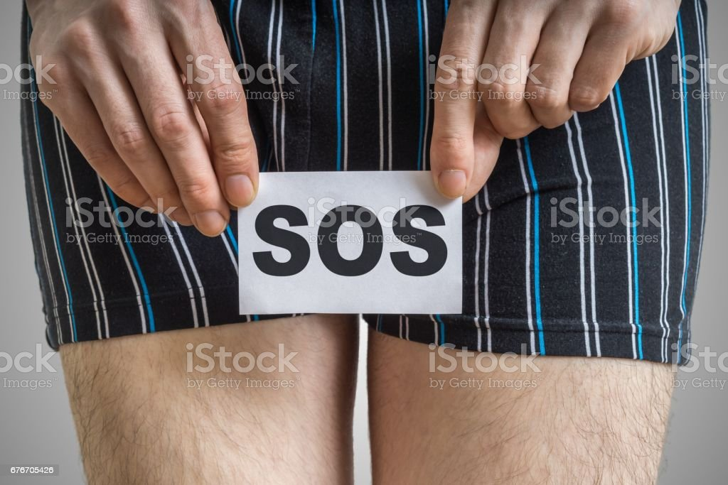 Urinary or prostate problems concept. Young man holds paper with SOS above crotch. stock photo