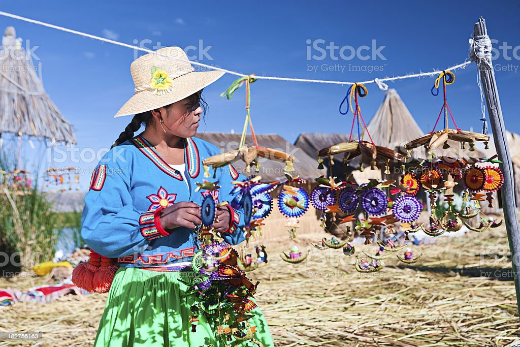 Uros woman selling souvenirs on floating island stock photo