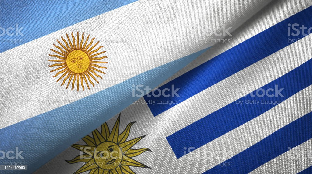 Uruguay and Argentina two flags together textile cloth, fabric texture stock photo