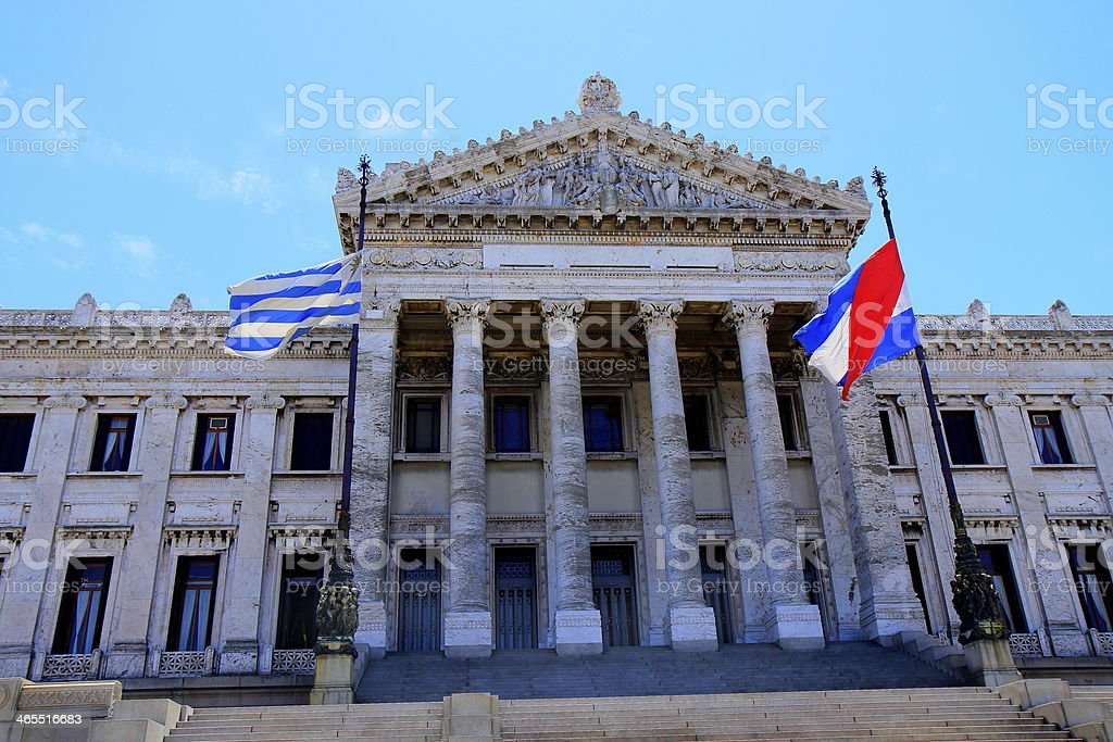 Uruguay classical Parliament in Montevideo and Uruguaian flags blue sky stock photo