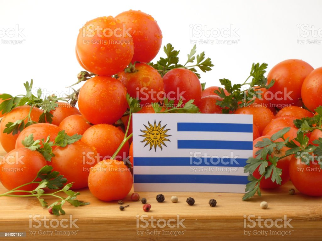 Uruguay flag on a wooden panel with tomatoes isolated on a white background stock photo