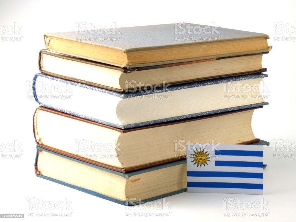 Uruguay flag with pile of books isolated on white background stock photo