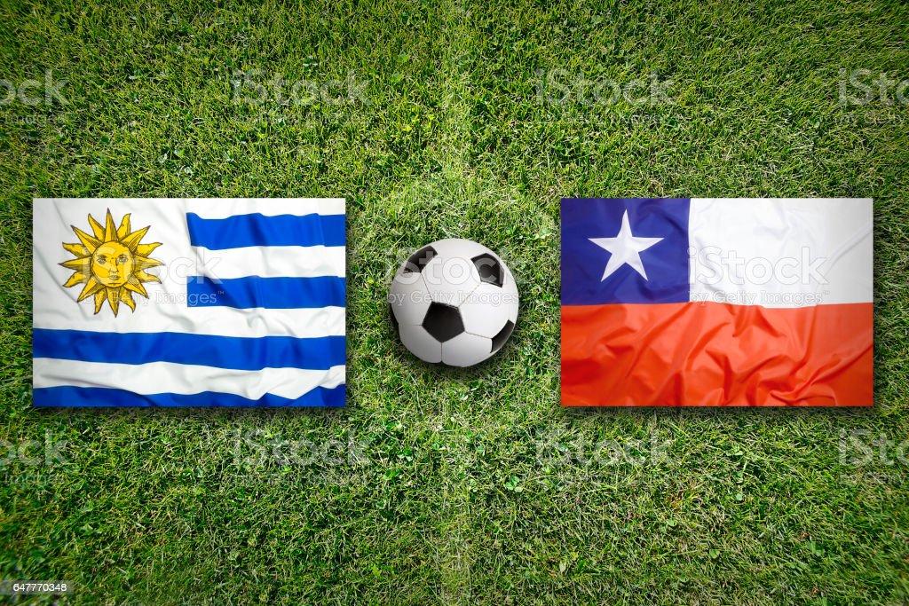 Banderas de Uruguay vs Chile en el campo de fútbol - foto de stock