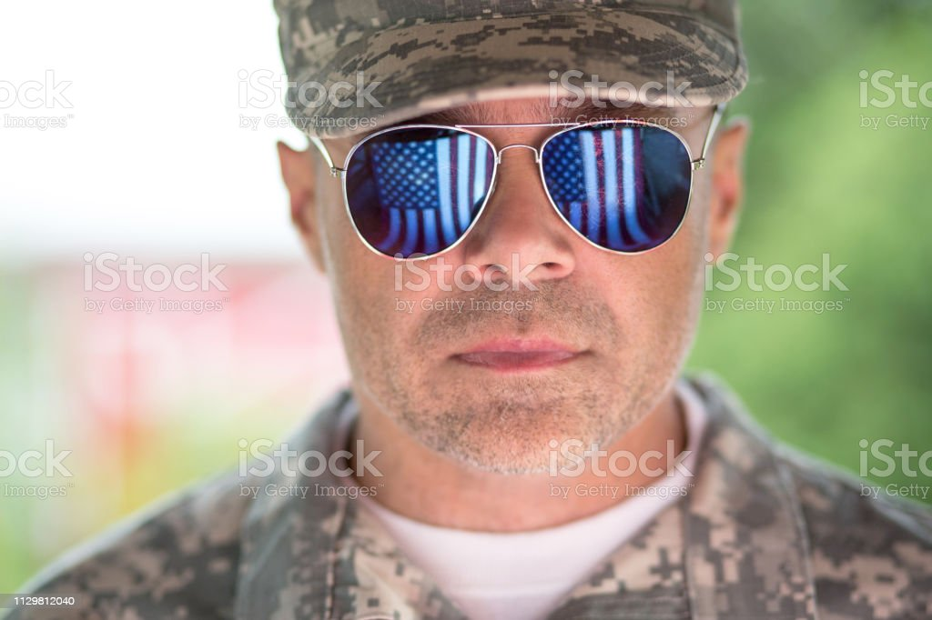 Proud us army soldier with american flag in sunglasses reflection