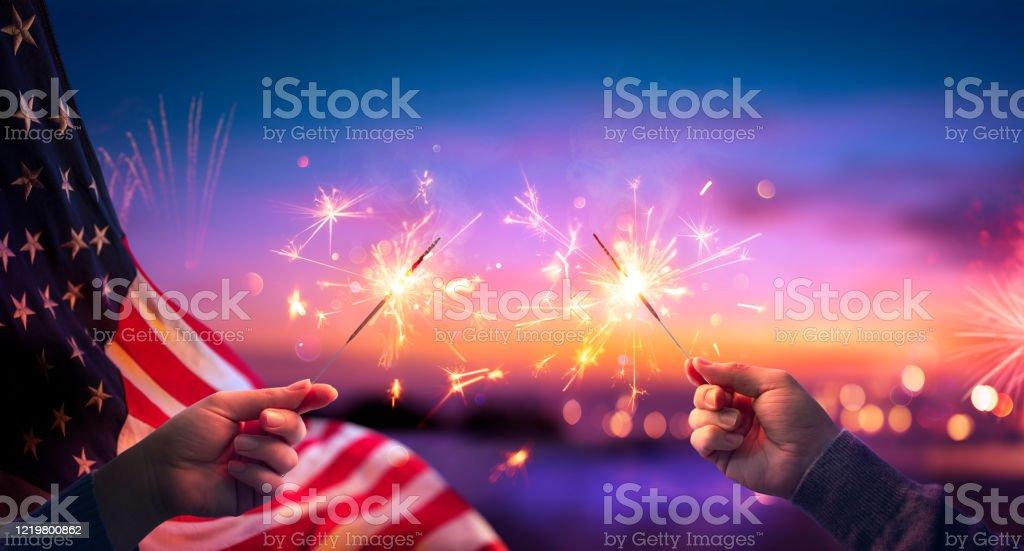 Usa Celebration With Hands Holding Sparklers And American Flag At Sunset With Fireworks Usa Celebration With Hands Holding Sparklers And American Flag At Sunset With Fireworks Abstract Stock Photo