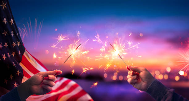 Usa Celebration With Hands Holding Sparklers And American Flag At Sunset With Fireworks stock photo