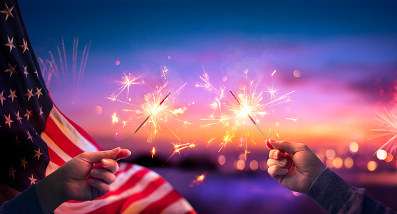 Usa Celebration With Hands Holding Sparklers And American Flag At Sunset With Fireworks Stock Photo - Download Image Now
