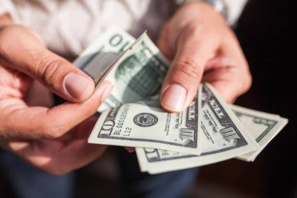 us-dollar in händen - agrobacter stock-fotos und bilder