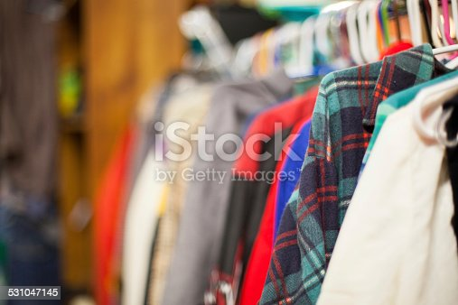 Image of used clothing on racks inside of a thrift store in Portland Oregon. Focus is on the blue and green flannel, and blurs out the remaining background. Thrift store shopping is a growing industry in Portland and many new second hand stores are popping up. Many locals enjoy purchasing second hand clothes for the fashion statement.