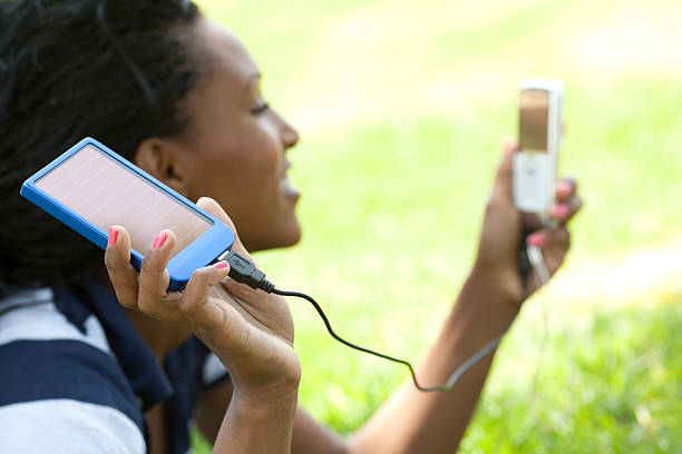 Use green energy -  solar charger Young woman uses solar charger panel to charge her cellphone. battery charger stock pictures, royalty-free photos & images