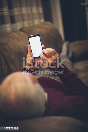 Use his time to correspond with his family. Senior man using smart phone at home.