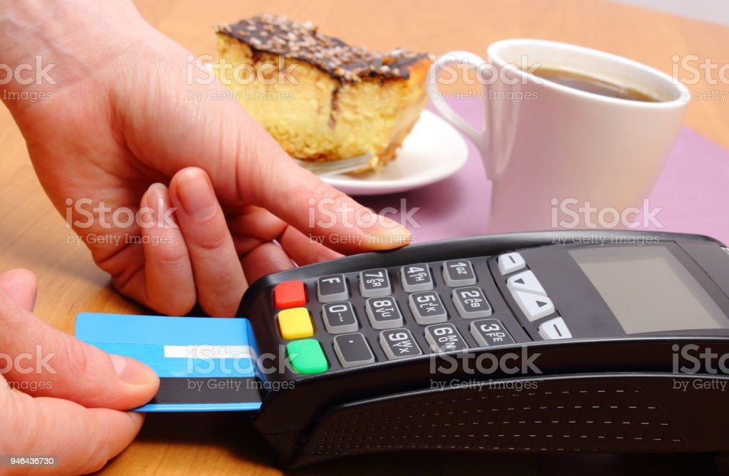 Use payment terminal for paying for cheesecake and coffee in cafe stock photo