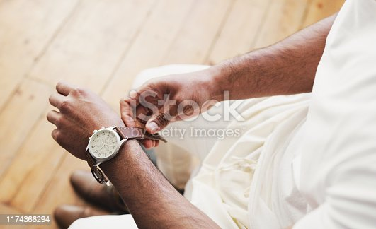 Shot of an unrecognizable man putting on a watch in preparation for his wedding