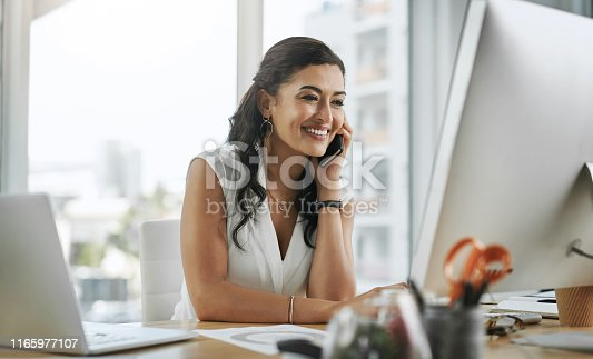Shot of a young businesswoman using a smartphone and computer in a modern office