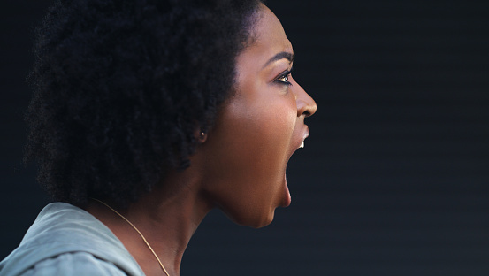 Cropped shot of a woman shouting against a dark background