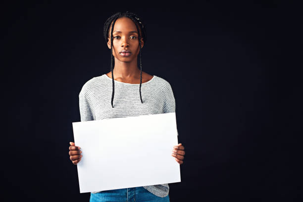 Use your voice to bring about change Studio shot of a beautiful young woman holding a blank placard against a black background social justice concept stock pictures, royalty-free photos & images