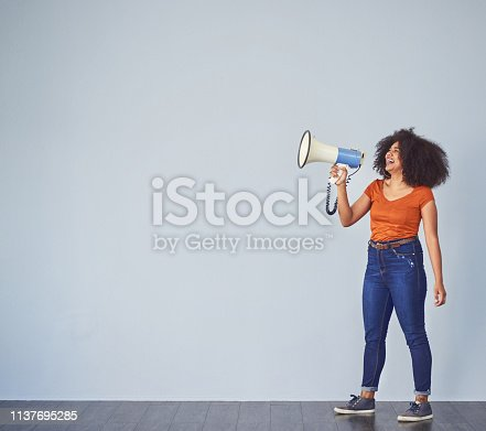 Studio shot of a young woman using a megaphone against a gray background