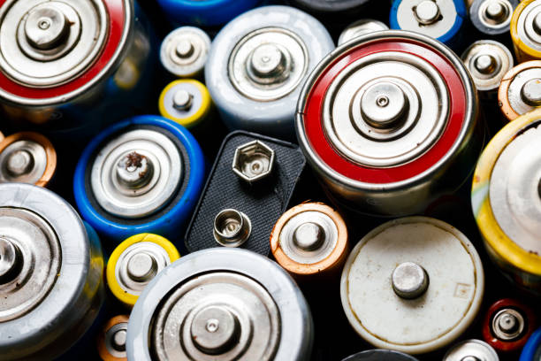 Used Alkaline batteries toxic waste recycling and ecology issues concept background stock photo