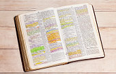 istock A Used and Highlighted Bible Open on a White Wood Table 1319269114