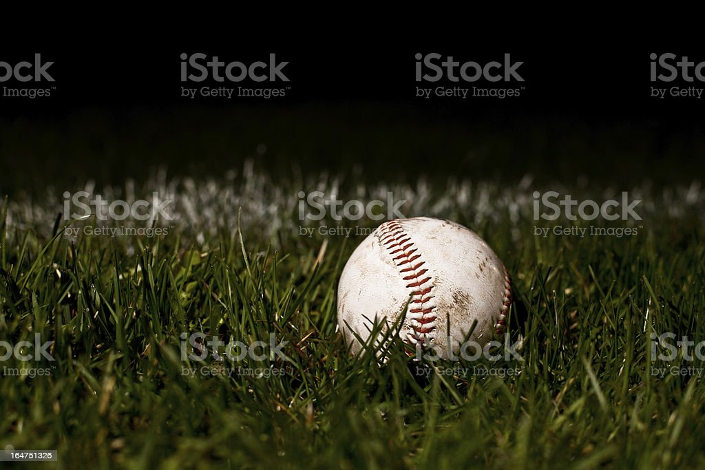 A used baseball laid on fresh green grass. stock photo