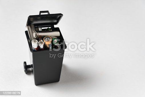 istock Used batteries in garbage container on white background. Proper disposal of batteries and accumulators. 1223518279