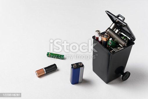 istock Used batteries in the garbage container on white background. Electronic waste concept. Eco-friendly disposal. 1223518281