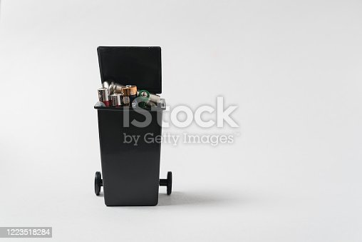 istock Used batteries in the garbage container on white background. Environmental pollution with toxic household waste 1223518284