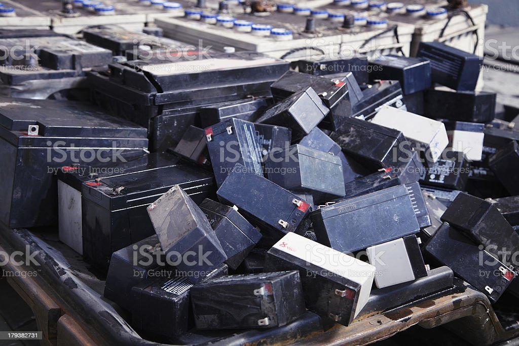Used batteries piled randomly in big container stock photo