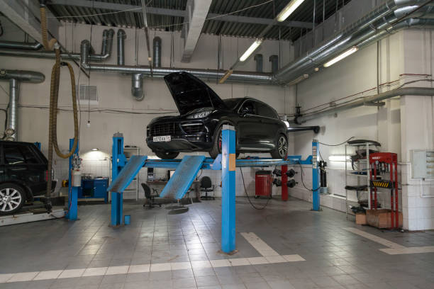 Used black car Porsche Cayenne with an open hood raised on a four-post lift for repairing the chassis and engine in a vehicle repair shop. Auto service industry. Novosibirsk, Russia - 08.01.2018: Used black car Porsche Cayenne with an open hood raised on a four-post lift for repairing the chassis and engine in a vehicle repair shop. Auto service industry. porsche stock pictures, royalty-free photos & images