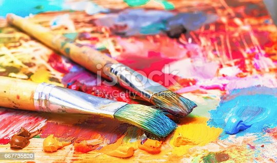 636761588istockphoto Used brushes on an artist's palette of colorful oil paint for drawing 667735820