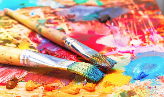 636761588 istock photo Used brushes on an artist's palette of colorful oil paint for drawing 667735820