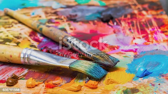 istock Used brushes on an artist's palette of colorful oil paint 636761588