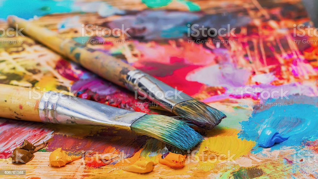 Used brushes on an artist's palette of colorful oil paint stock photo