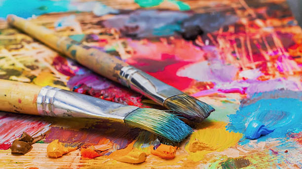 used brushes on an artist's palette of colorful oil paint - kunst stockfoto's en -beelden