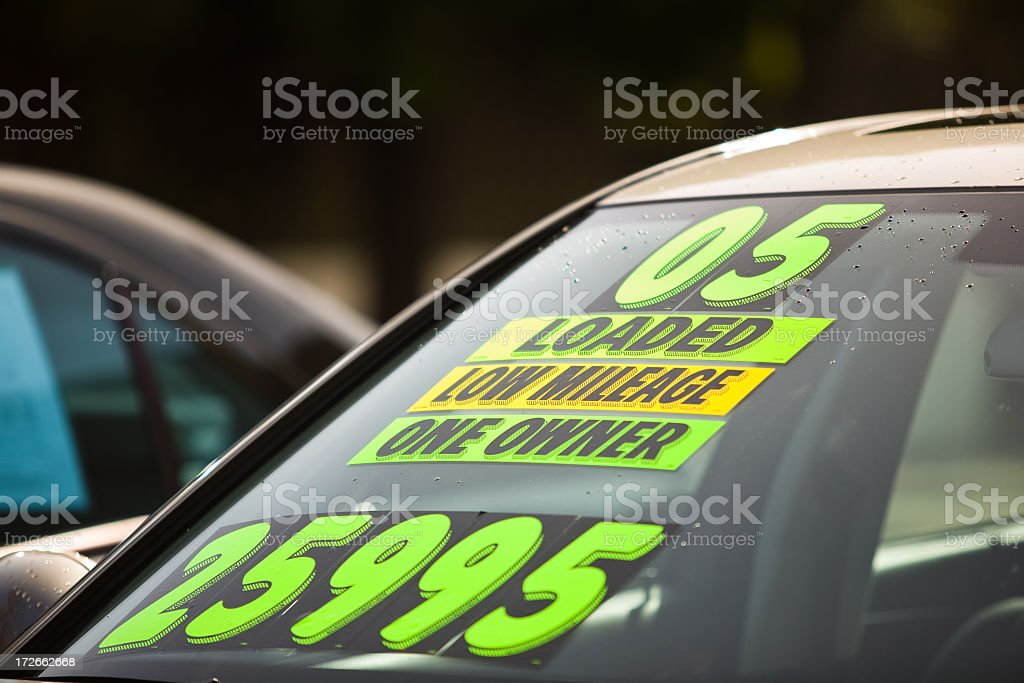 Used Car Dealership Stickers on the windshield of a car for sale at a used car dealership 2005 Stock Photo