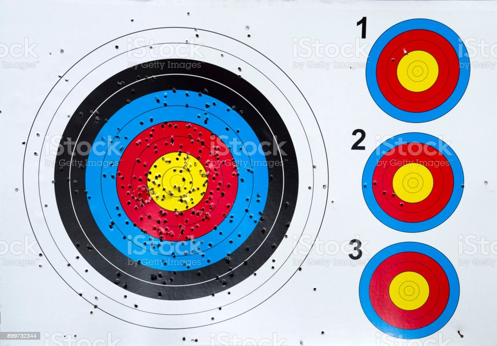 Used cardboard colorful four targets with holes closeup stock photo