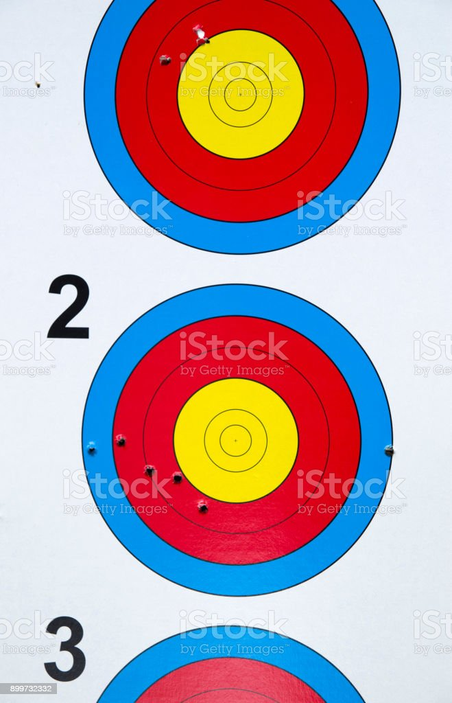 Used cardboard three colorful targets with holes closeup stock photo