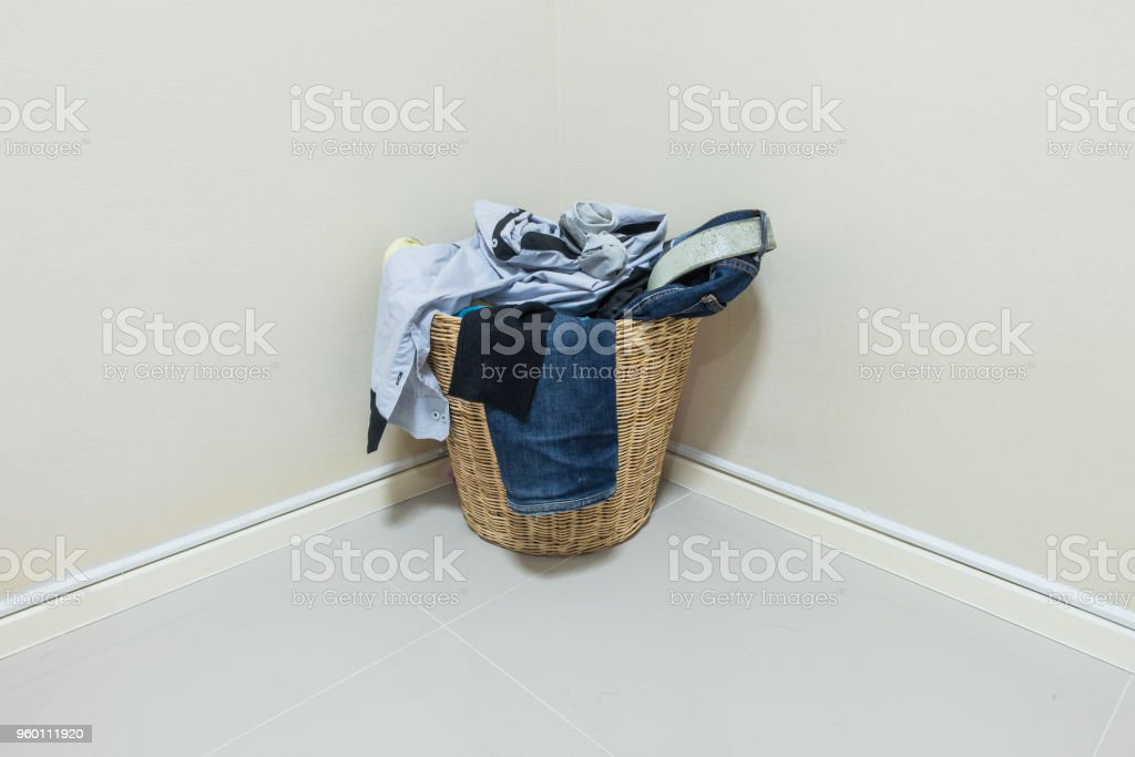 Used clothes in wood basket at corner in room stock photo