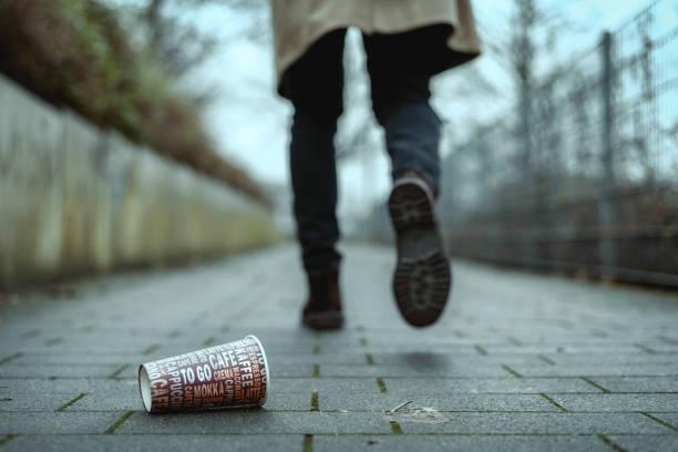 Gebrauchte Kaffeebecher auf dem Bürgersteig als Symbol für Umweltverschmutzung. – Foto