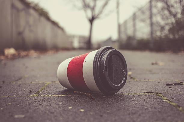 Used Coffee mug at sidwalk as symbol for pollution. – Foto