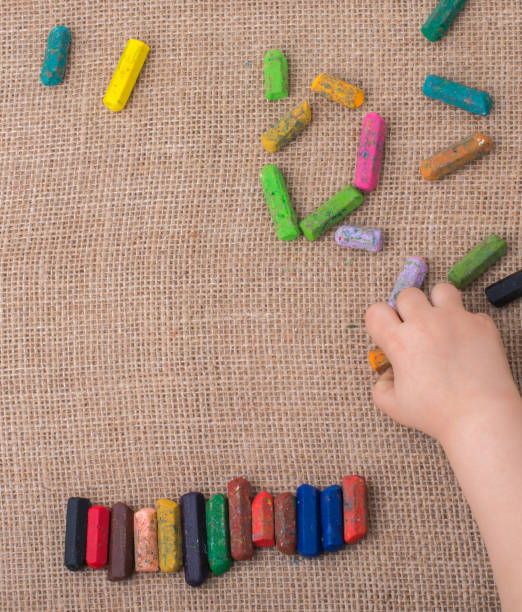 Used  color crayons and a toddlers hand stock photo