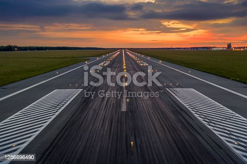 Used concrete asphalt airport empty runway with many braking marks, markings for landings and all navigation lights on