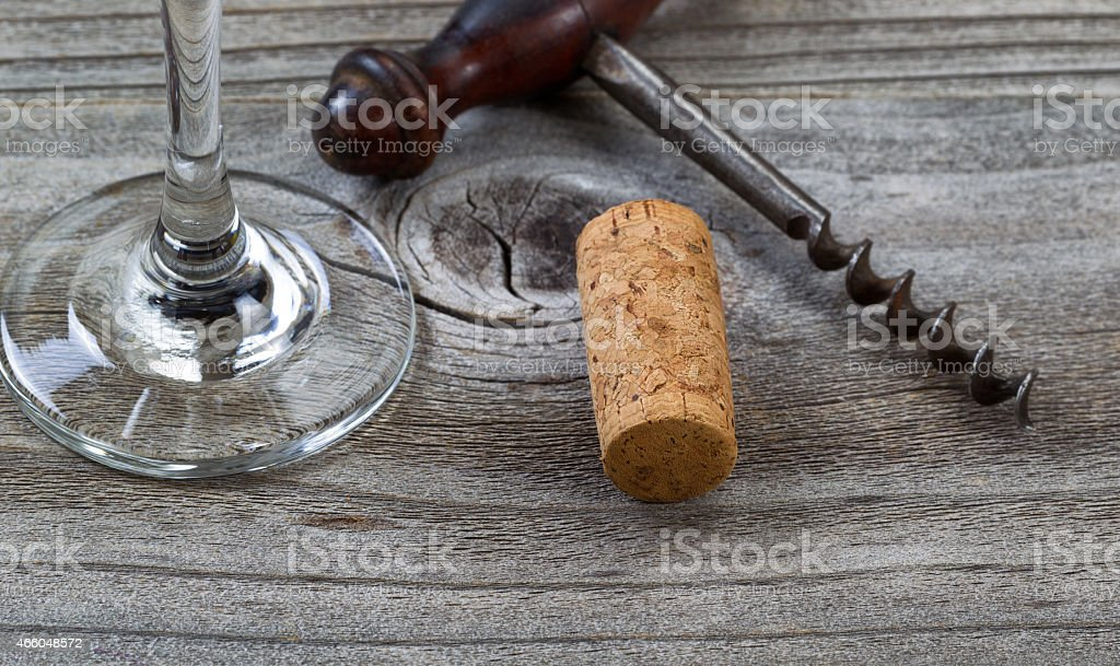 Used cork with corkscrew and wine glass stock photo