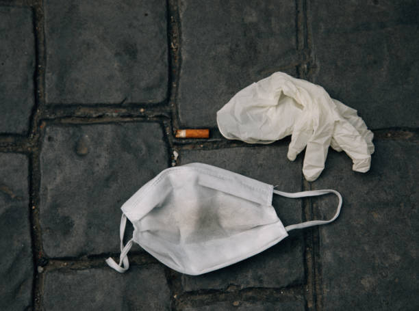 Used, dirty and old medical mask and glove lies on the street like a garbage stock photo