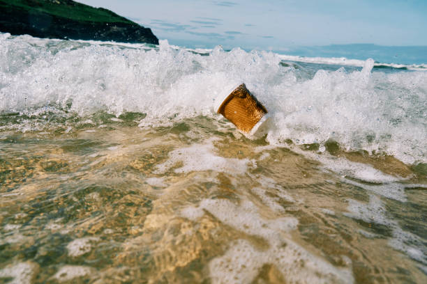 used discarded paper coffee cup caught in a wave on the sea surface. - trash stock pictures, royalty-free photos & images