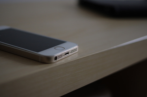 Used gold iPhone 5 with white panel and thunderbolt interface on light yellow wooden table