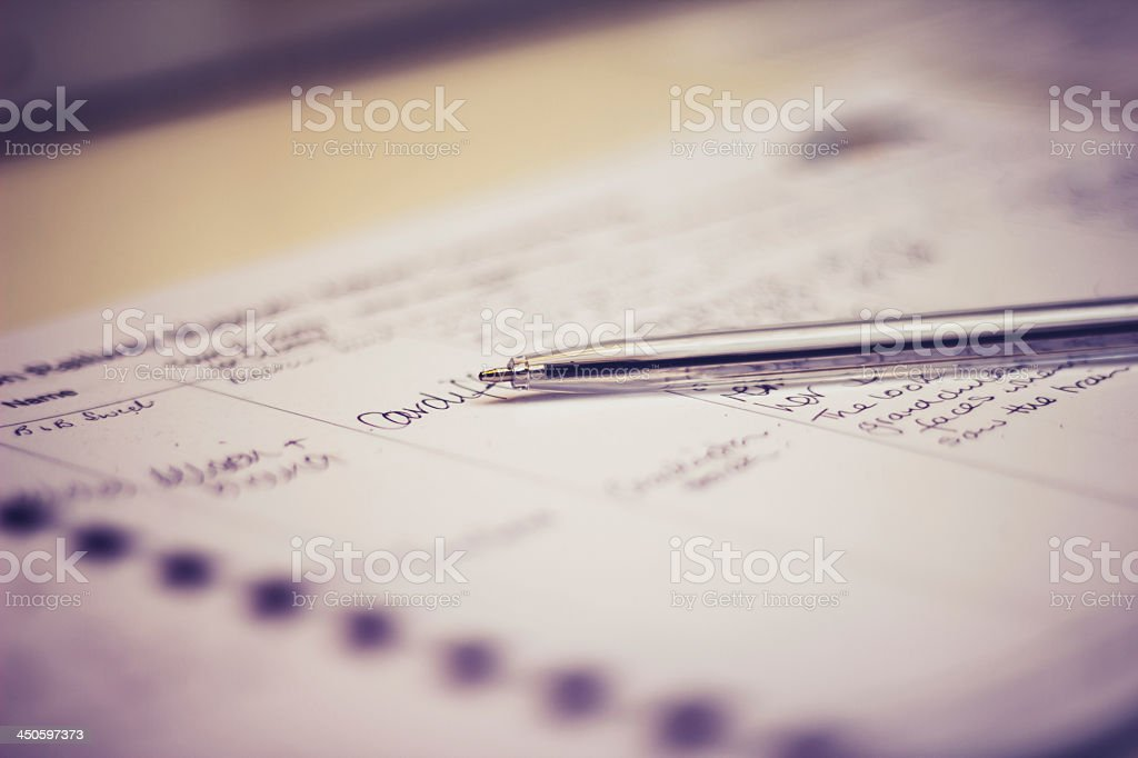 Used guestbook with a silver pen in dimmed lighting stock photo