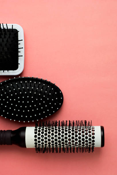 Used Hair brush tools on pink or coral background with copy space. Beauty fashion, hair care background. Used Hair brush tools on pink or coral background with copy space. Beauty fashion, hair care board. hairbrush stock pictures, royalty-free photos & images