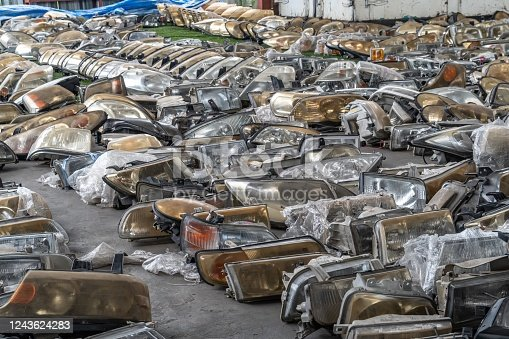 Used headlamp components for sale at scrapyard area
